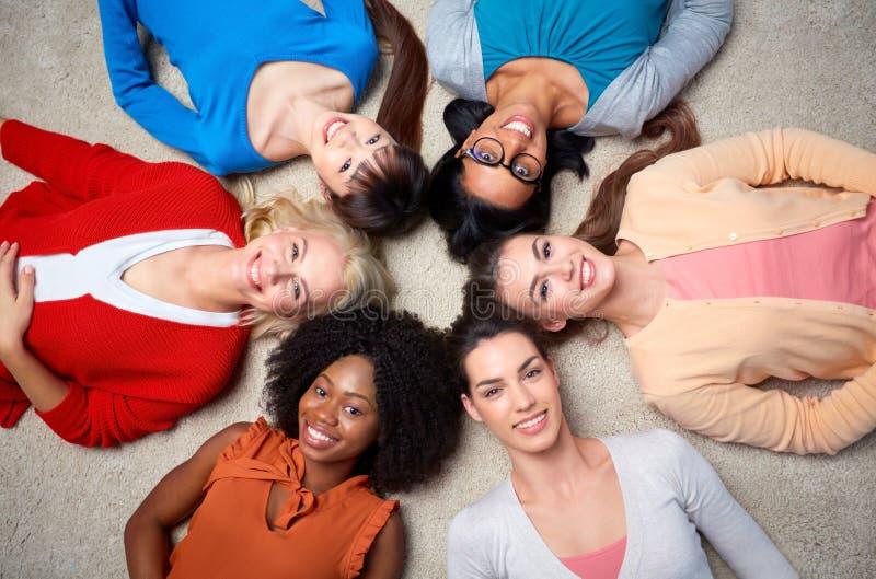 Internationell grupp av lyckliga kvinnor som ligger på golv arkivbild