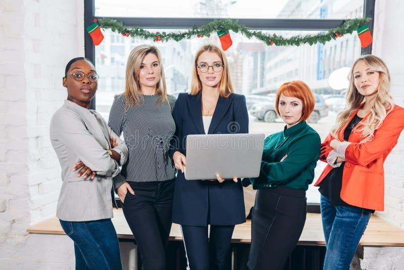 Internationell grupp av lyckliga kvinnor som står med bärbar datorståenden royaltyfri fotografi