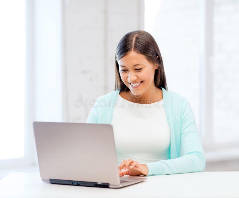 Internationell studentflicka med bärbara datorn på skolan royaltyfri bild