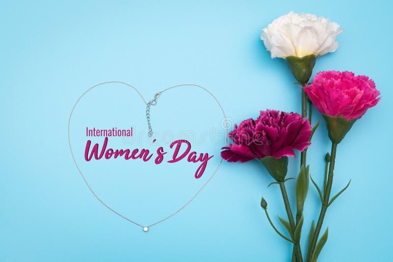 Internationell Women's dag med blommor och hjärtaformhalsbandet på blå bakgrund arkivbild