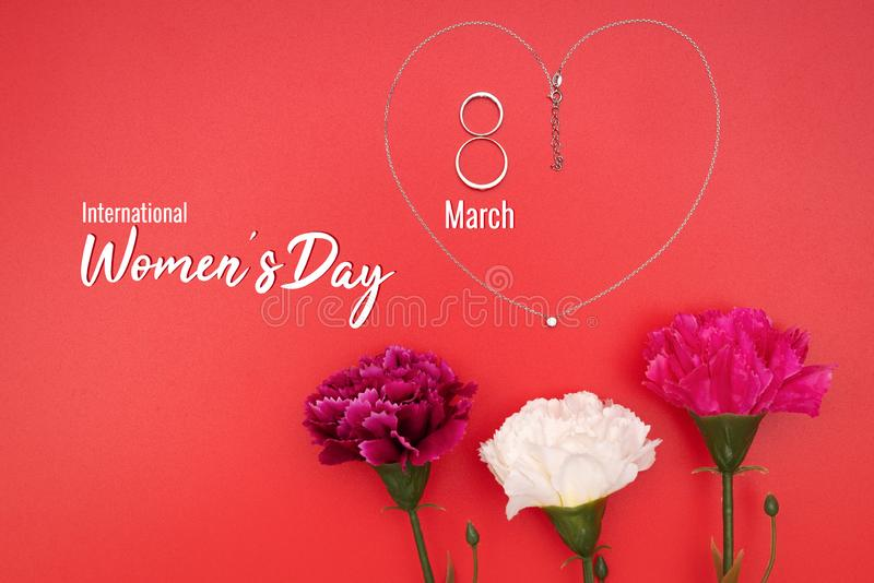 Internationell Women's dag med blommor och hjärtaformhalsbandet på röd bakgrund royaltyfri bild