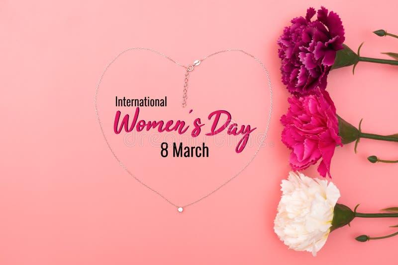 Internationell Women's dag med blommor och hjärtaformhalsbandet på rosa bakgrund arkivfoto
