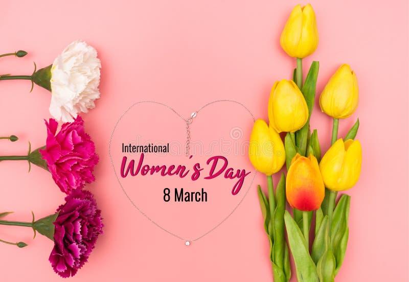 Internationell Women's dag med blommor och hjärtaformhalsbandet på rosa bakgrund arkivbild