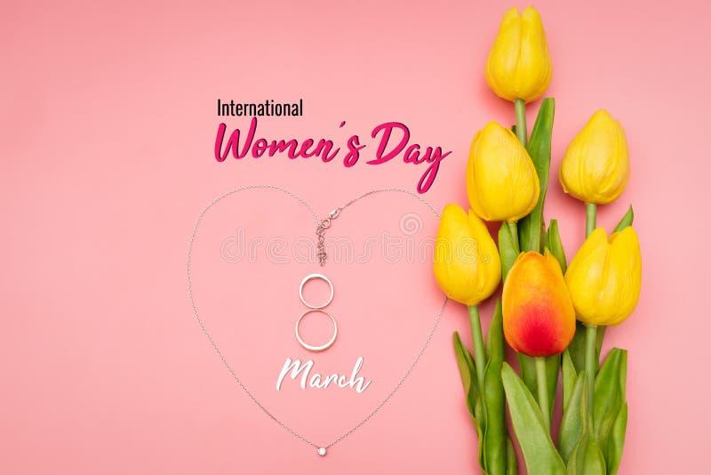 Internationell Women's dag med blommor och hjärtaformhalsbandet på rosa bakgrund royaltyfri bild