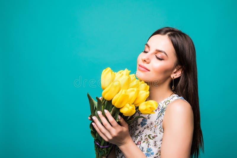 Internationella kvinnor dag, åtta marsch Härlig stående av den nätta kvinnan med gula tulpan i elegant klänning på blå bakgrund M royaltyfri bild