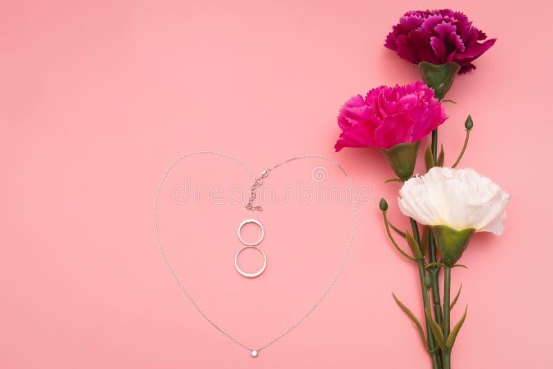 Internationella kvinnors dag med blommor och hjärtaformhalsbandet på rosa bakgrund arkivbild