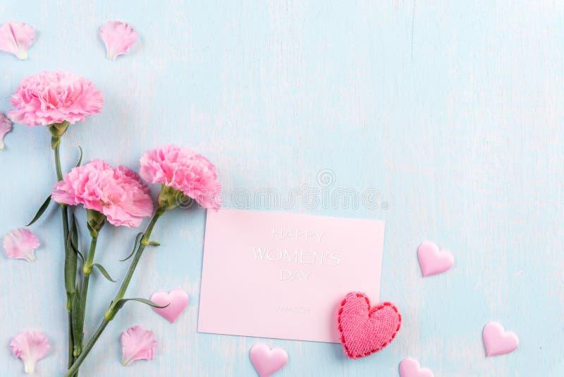 Internationellt begrepp för dag för kvinna` s Rosa nejlikablomma med text för mars 8 på rosa papper på blå pastellfärgad träbakgr royaltyfria bilder