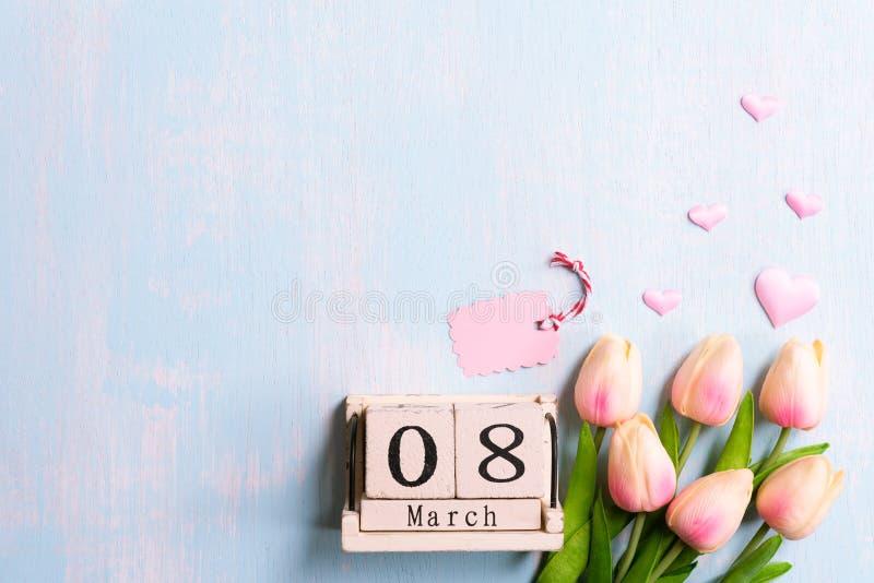 Internationellt begrepp för dag för kvinna` s Rosa tulpan och pappers- hjärtor med text för mars 8 på träkvarterkalender på blått arkivbilder