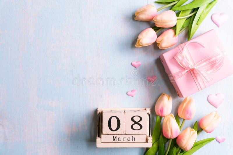 Internationellt begrepp för dag för kvinna` s Rosa tulpan och pappers- hjärtor med text för mars 8 på träkvarterkalender på blått royaltyfri fotografi