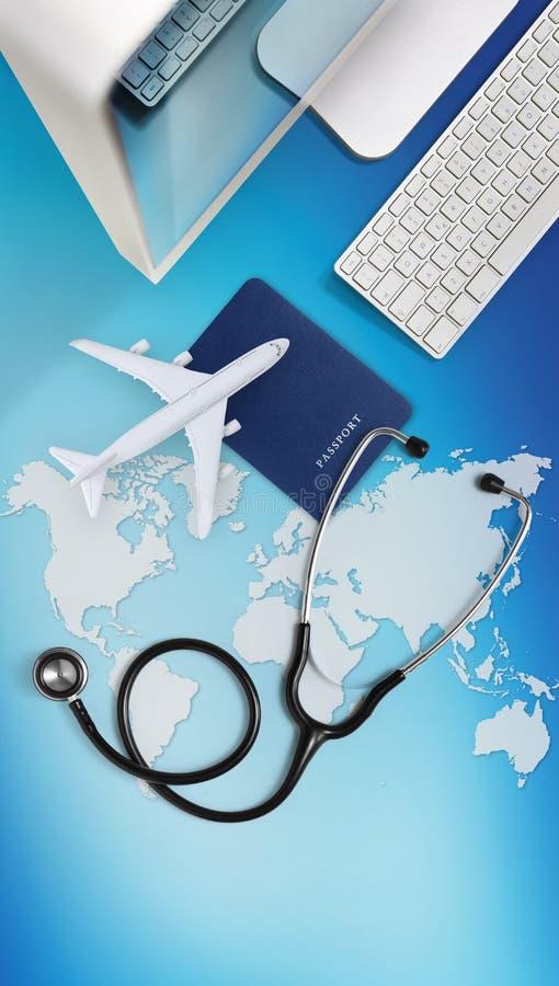 Internationellt medicinskt loppförsäkringbegrepp, stetoskop, pass, dator och flygplan på himmelbakgrund med den globala översikte arkivfoton