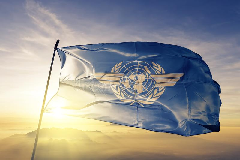 Internationellt tyg för torkduk för textil för flagga för civilflygorganisation som ICAO vinkar på den bästa soluppgångmistdimman royaltyfri illustrationer