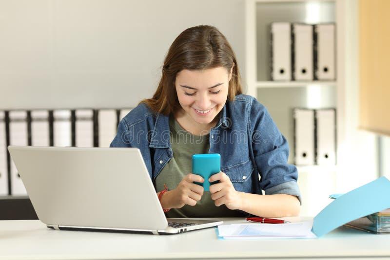 Interne el mensaje de la lectura en un teléfono elegante en la oficina fotos de archivo