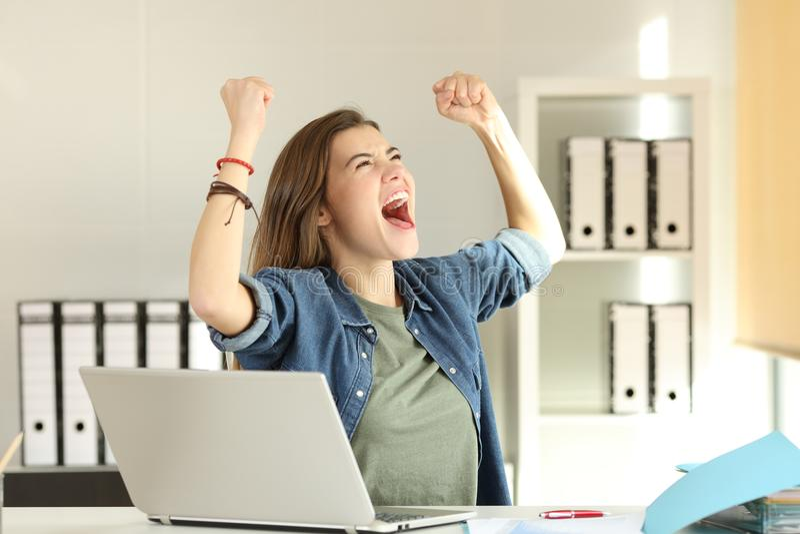 Interne enthousiaste célébrant le succès au bureau images stock