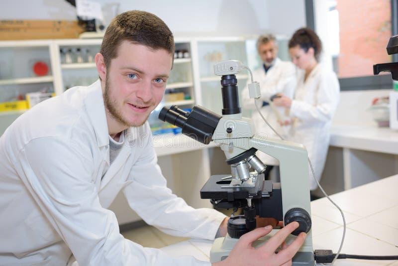 Internera att posera, medan rymma mikroskopet royaltyfri bild