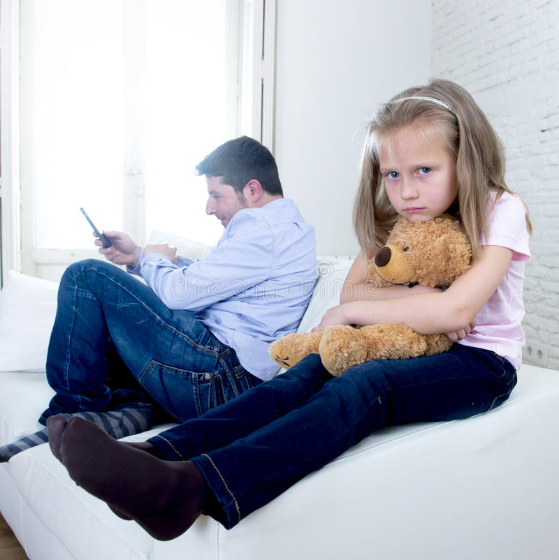 Internet addict father using mobile phone ignoring little sad daughter bored hugging teddy bear. Young internet addict father using mobile phone ignoring little royalty free stock photos