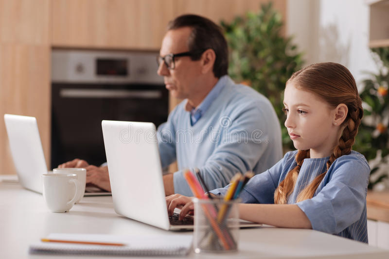 Internet addicted grandfather and granddaughter using laptops indoors stock photos