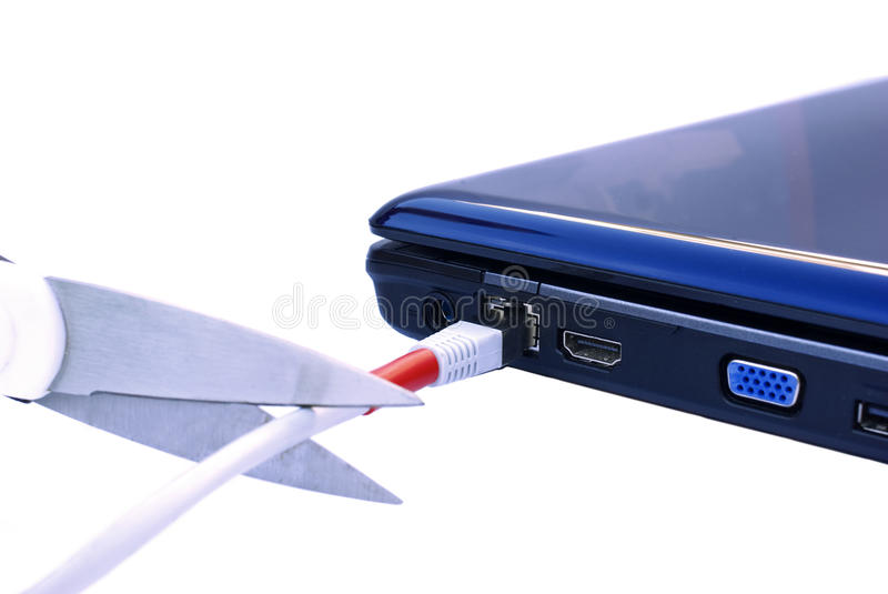 Broken Internet addiction. Concept, scissors cutting network cable on a notebook royalty free stock photo