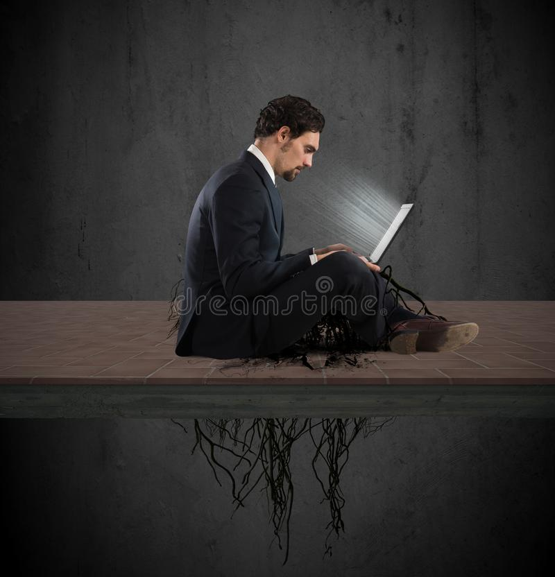 Internet addiction concept. Businessman sitting with his laptop with roots under royalty free stock image
