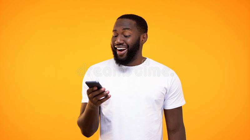 Internet africain stupéfait de smartphone de lecture rapide d'homme, programme d'application temps réel, argent liquide de retour photos stock