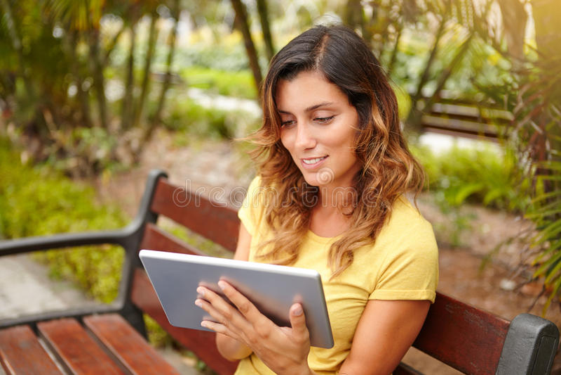 Internet alegre de la ojeada de la mujer en la tableta imagen de archivo libre de regalías