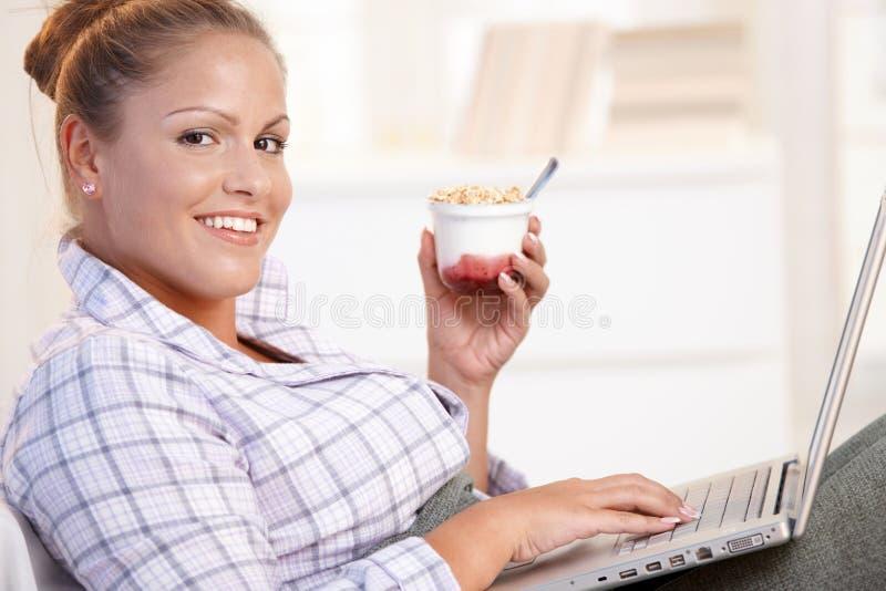 Internet bonito de la ojeada de la muchacha en la sonrisa de la cama foto de archivo