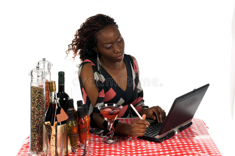 Internet Cafe. Pretty young African American business woman working on a laptop computer while enjoying a beverage at an Internet Cafe royalty free stock photo