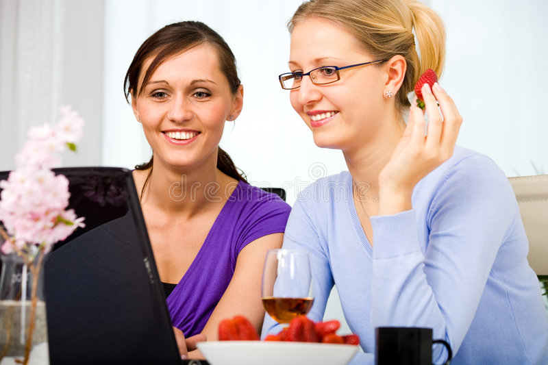 Internet cafe. Two young woman surfing internet at cafe royalty free stock photo
