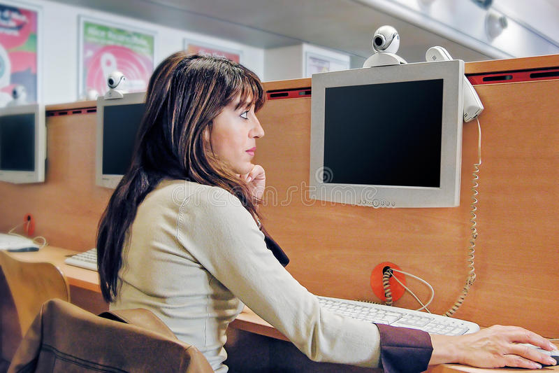 Internet cafe. A woman called in video conference using a PC connected to the network, the webcam and the phone in an internet cafe royalty free stock images