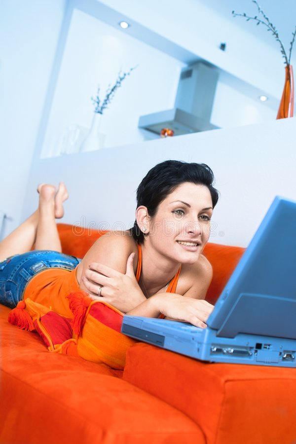 Internet chat. Young women is resting on the couch and surfing the internet on her laptop computer