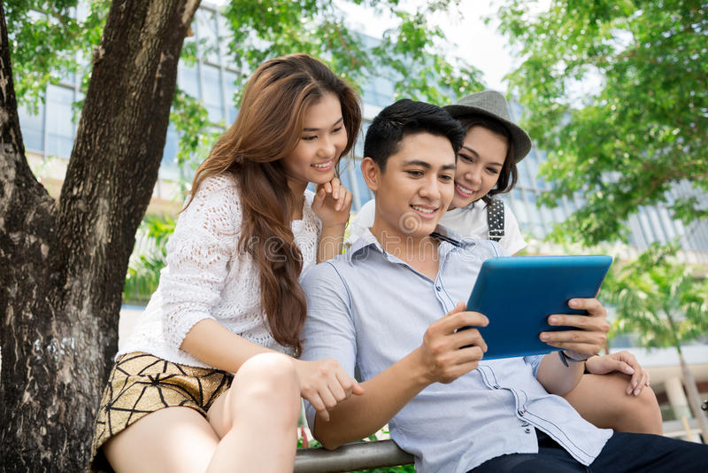 Internet chatting. A group of friends with a tablet outside stock photo