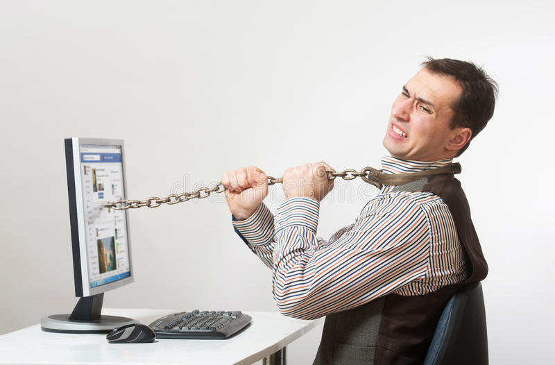 Internet and computer addiction. Man chained to his computer royalty free stock photography