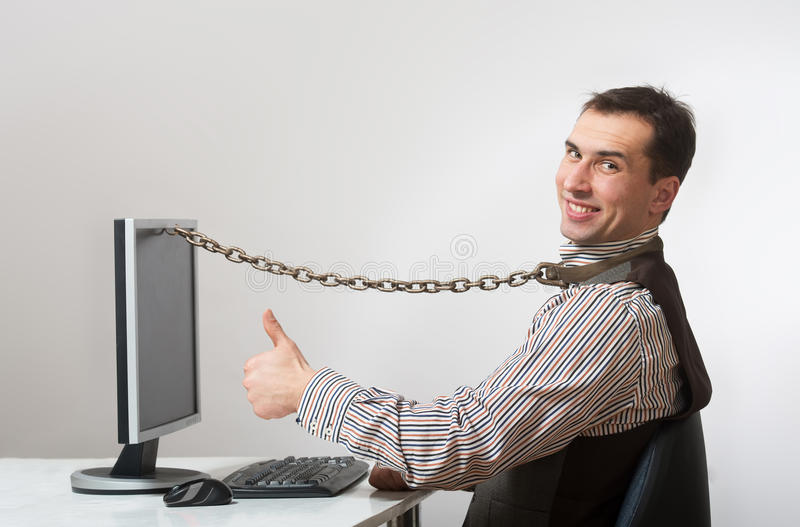 Internet and computer addiction. Smiling man chained to his computer royalty free stock images