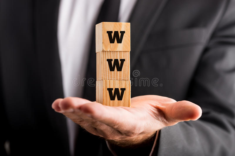 Internet concept. With a businessman holding a stack of three wooden cubes with the letters www balanced on his palm royalty free stock photos