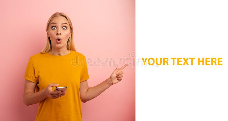 Blonde cute girl, with her smartphone, indicates something. Amazed and surprised expression face. Pink background with stock photo