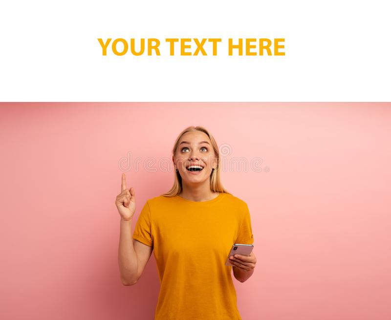 Blonde cute girl, with her smartphone, indicates something. Amazed and surprised expression face. Pink background with stock image