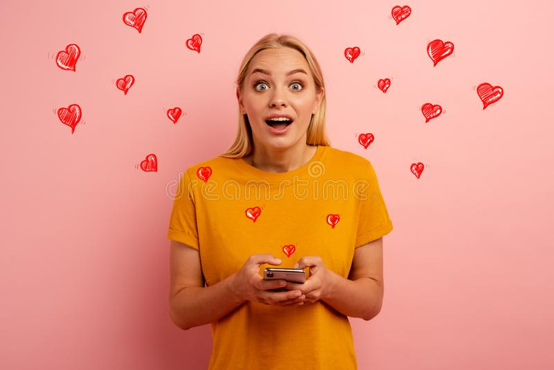 Blonde cute girl receives hearts on her smartphone. Happy and surprised expression face. Pink background royalty free stock photo