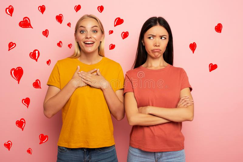 Friends receives likes and hearts from social network. But the blonde is happy and the brunette is not. Pink background royalty free stock photo