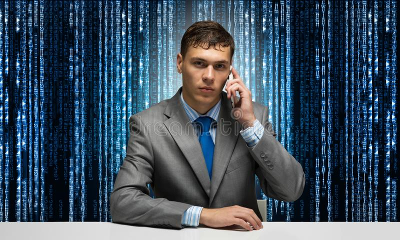 Internet consultant talking on phone. Businessman sitting at desk on background binary computer code. Portrait of hosting service manager wears business suit royalty free stock images