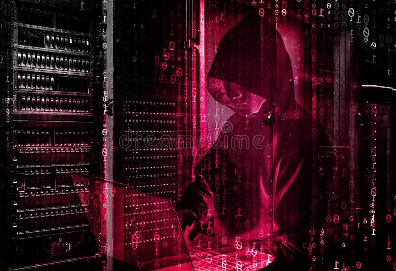 Internet crime concept. Male figure with hood on red wall background. Hacker concept. royalty free stock photos