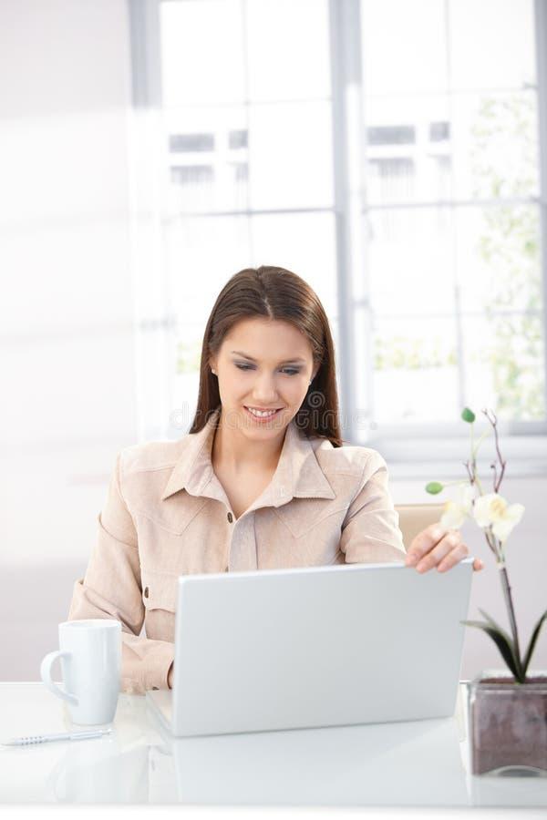 Internet da consultação da mulher nova em casa foto de stock