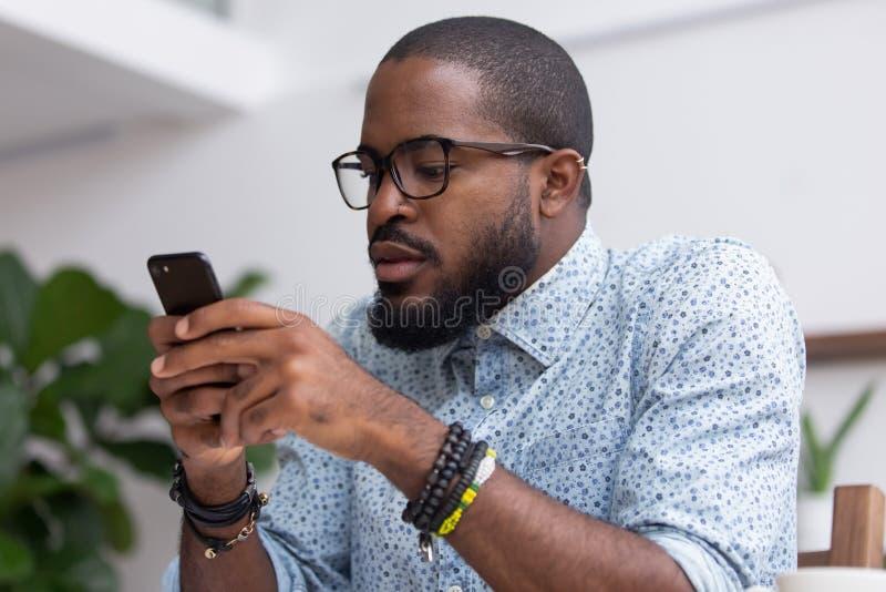 Internet de charla de la ojeada del hombre negro del retrato usando el teléfono móvil imágenes de archivo libres de regalías