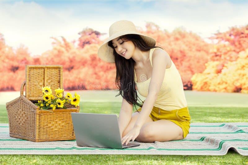 Internet de lecture rapide de femme avec l'ordinateur portable au parc photos libres de droits