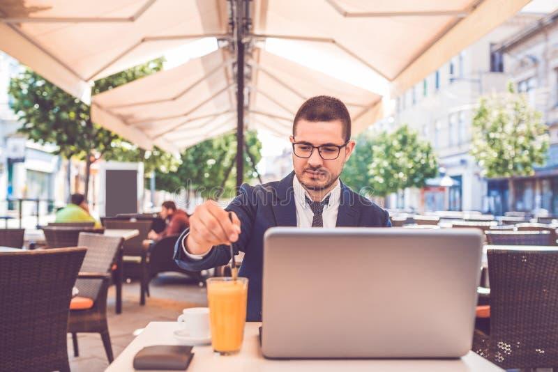 Internet de lecture rapide de jeune homme sur son ordinateur portable et jus potable dans la ville images stock