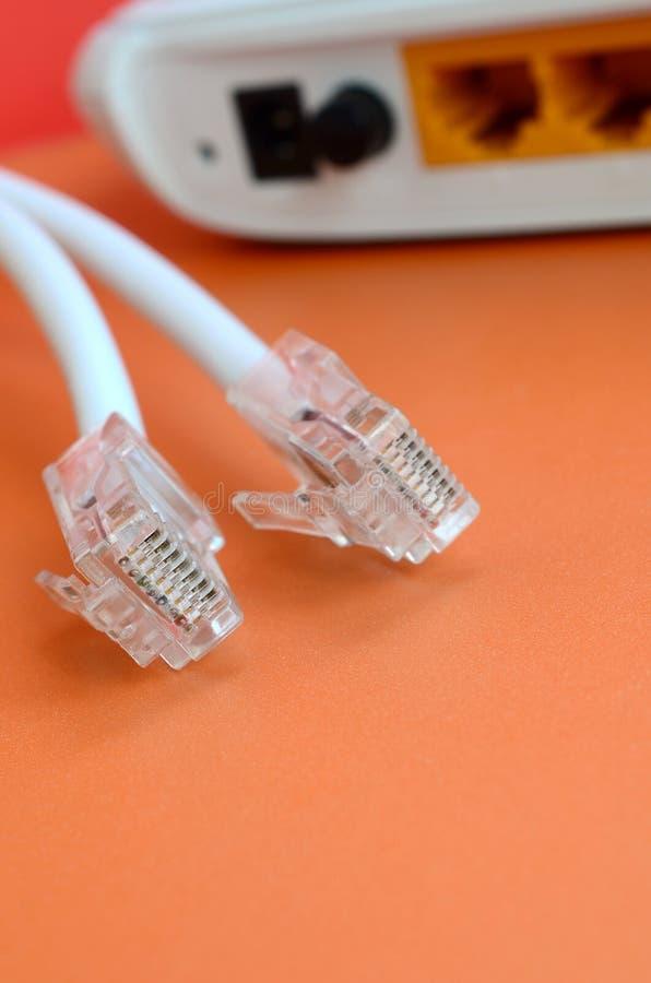 Internet-de router en Internet-de kabelstoppen liggen op een heldere sinaasappel royalty-vrije stock foto's