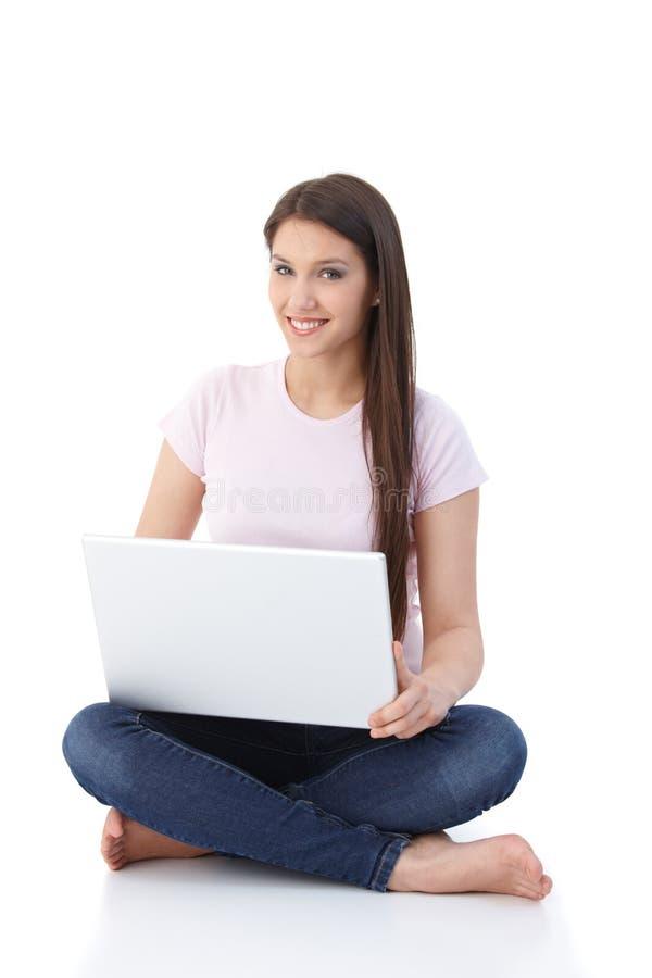 Internet de sorriso da consultação da mulher no assoalho fotos de stock