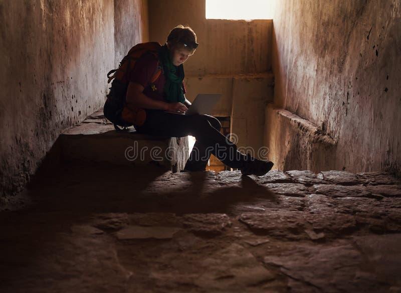 Internet de touristes de ressac d'homme avec l'ordinateur portable dans le vieux château du Thibet photographie stock libre de droits