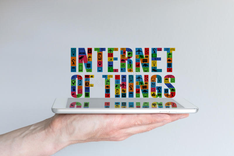 Internet del concepto de las cosas (IoT) Fondo con la tableta de la tenencia de la mano y el texto flotante en diversos colores y fotos de archivo