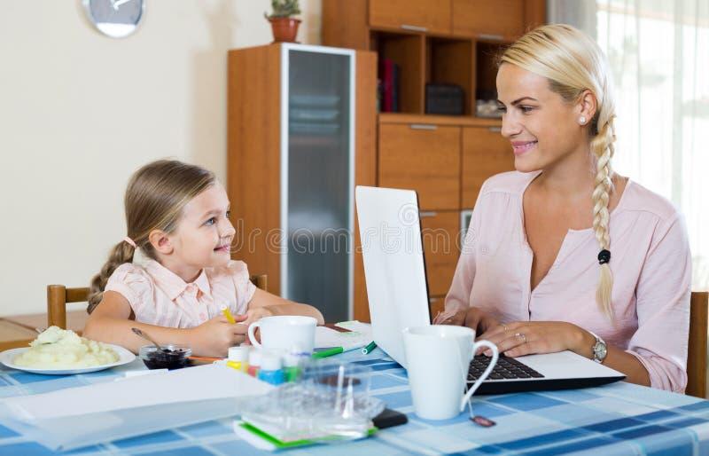 Internet di lettura rapida della donna di affari a casa, figlia che assorbe p fotografia stock