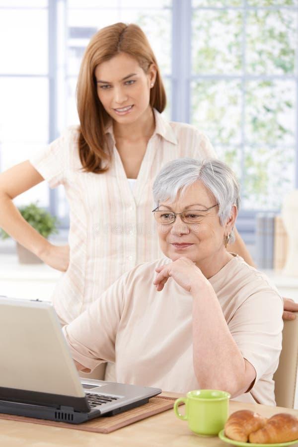Internet di lettura rapida della nonna con la nipote immagini stock libere da diritti