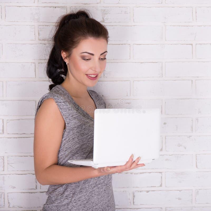 Internet en sociaal media concept - mooie vrouw die laptop met behulp van stock afbeelding